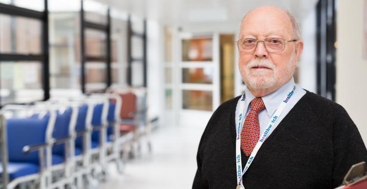 healthwatch representative standing in hospital corridor with clipboard