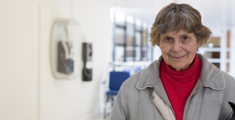 older woman standing in hospital corridor