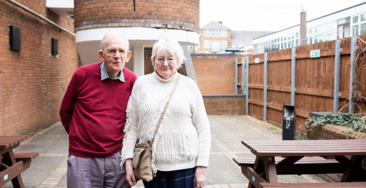 two older people standing outside looking into camera