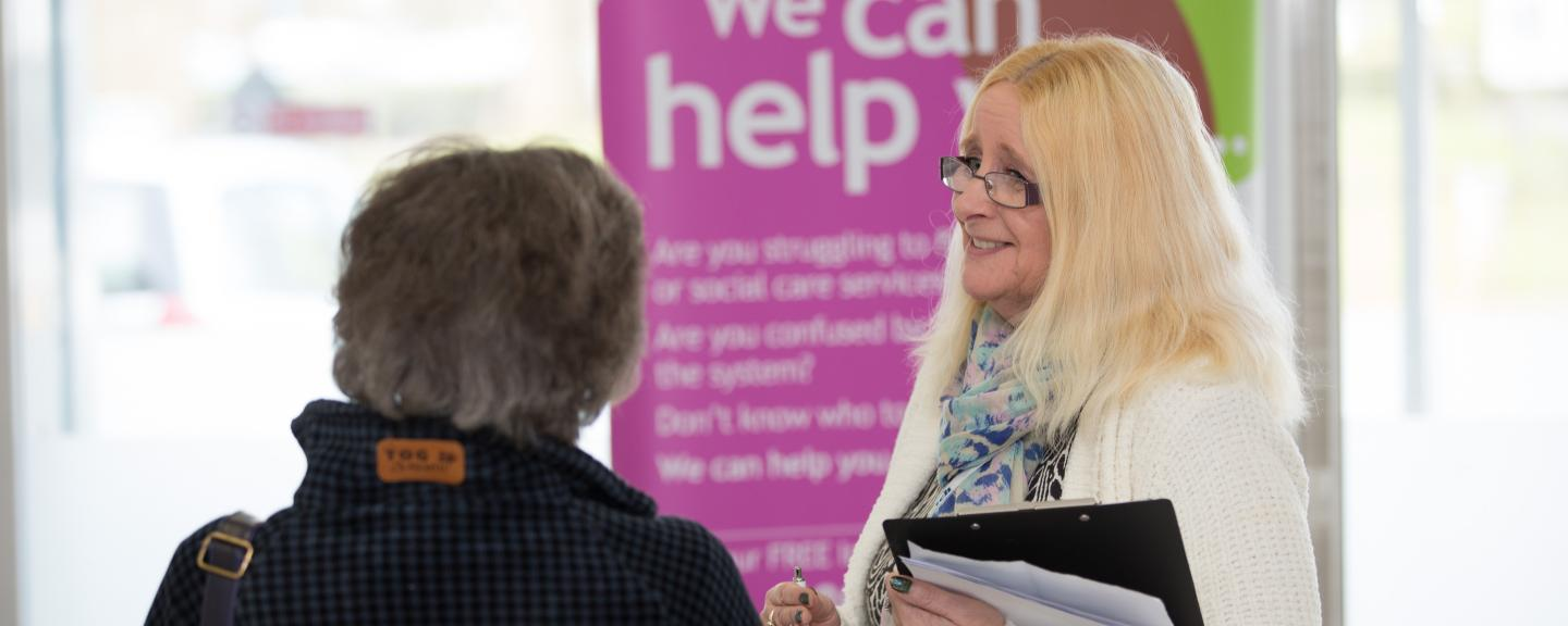 Woman standing in front of a banner that says 'we can help' speaking to a member of the public
