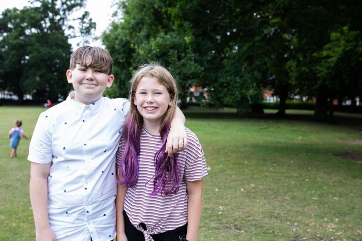 two children standing in a park