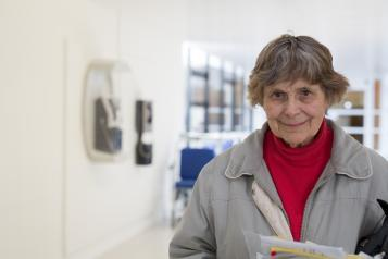 older woman standing in hospital corridor