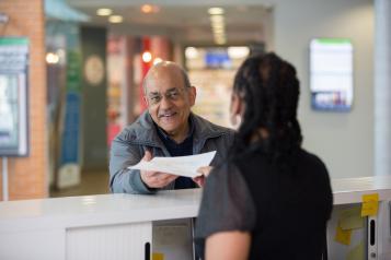 elderly man talking to receptionist