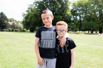 two boys stood in the park with their arms round each other