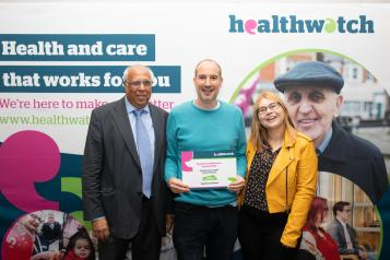 healthwatch sutton team holding certificate