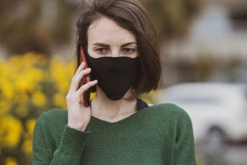 woman wearing a mask talking on a mobile phone