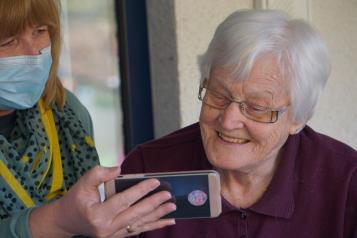 younger woman wearing a mask showing an older woman a phone