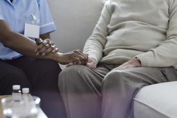 Nurse holding patient hand