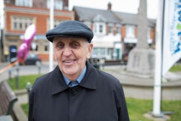 older man smiling at the camera whilst standing outside