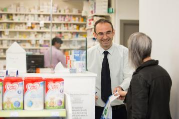 pharmacist handing out prescription
