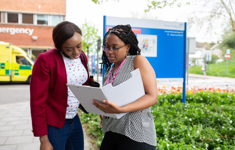 Two women standing outside a hospital looking at a document